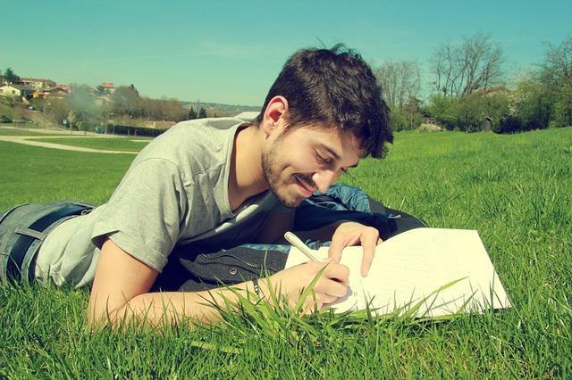 草むらで横になり、何かを書く男性
