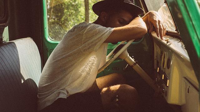 疲れて車で眠る男