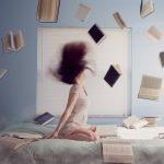 ベッドに座る女性と宙を舞う複数の書籍