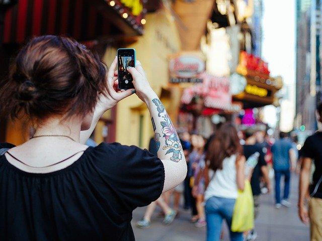 街中で写真を撮る女性
